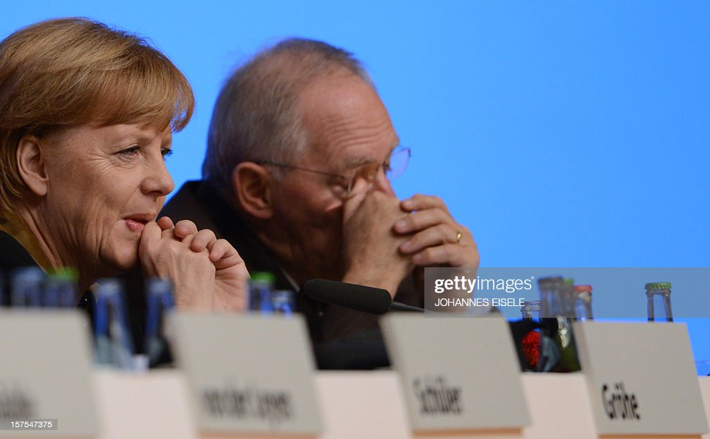 German Chancellor Angela Merkel and German Finance Minister Wolfgang Schaeuble attend a congress of Germany's ruling conservative Christian Democratic Union (CDU) party on December 4, 2012 in Hanover, central Germany. German Chancellor Angela Merkel was re-elected head of her conservative Christian Democrats (CDU) by more than 97 percent of delegates' votes at a two-day party congress. It was Merkel's best result since she took over as chairman of the CDU in 2000 and comes as she gears up for fighting for a third term at the helm of Europe's top economy in elections expected in September 2013.