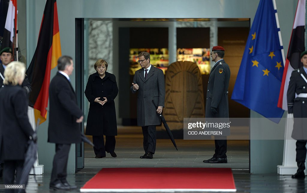 German Chancellor Angela Merkel (C-L) and German Foreign Minister Guido Westerwelle (C-R) wait to welcome the Egyption President expected at the Chancellery in Berlin on January 30, 2013. Egypt's President Mohamed Morsi flew to Berlin for talks with Chancellor Angela Merkel in a visit shortened to just a few hours after days of unrest in his country, official media said.