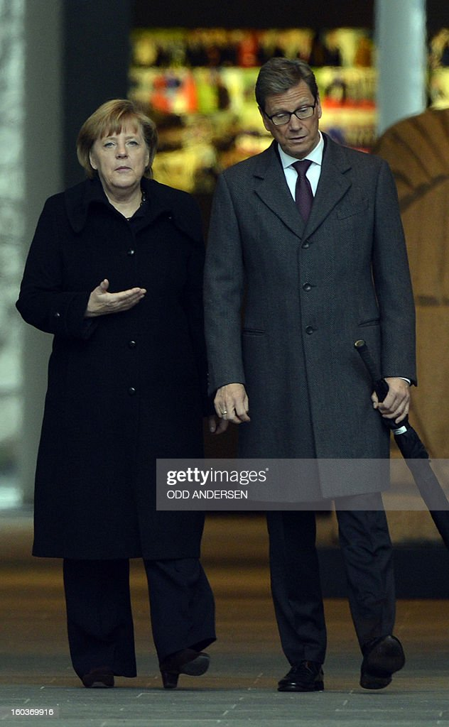 German Chancellor Angela Merkel (L) and German Foreign Minister Guido Westerwelle wait to welcome the Egyption President expected at the Chancellery in Berlin on January 30, 2013. Egypt's President Mohamed Morsi flew to Berlin for talks with Chancellor Angela Merkel in a visit shortened to just a few hours after days of unrest in his country, official media said. AFP PHOTO / ODD ANDERSEN