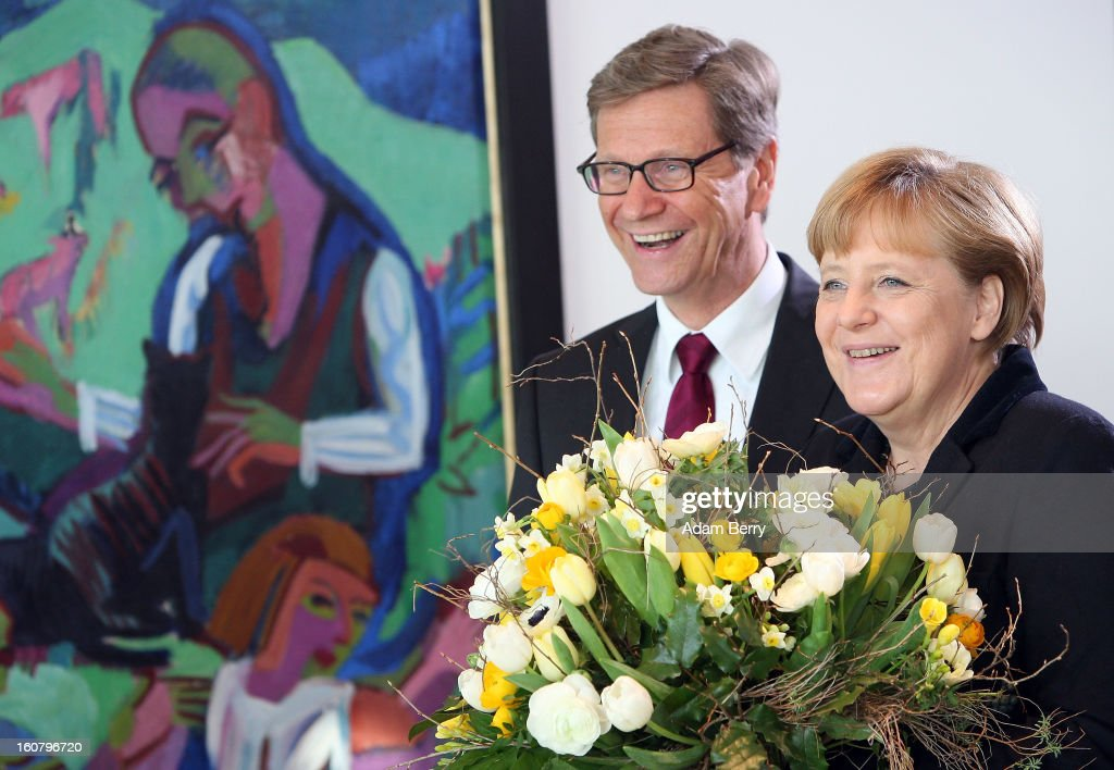 German Chancellor <a gi-track='captionPersonalityLinkClicked' href=/galleries/search?phrase=Angela+Merkel&family=editorial&specificpeople=202161 ng-click='$event.stopPropagation()'>Angela Merkel</a> (R) and German Foreign Minister <a gi-track='captionPersonalityLinkClicked' href=/galleries/search?phrase=Guido+Westerwelle&family=editorial&specificpeople=208748 ng-click='$event.stopPropagation()'>Guido Westerwelle</a> hold flowers to present to German Foreign Affairs Office State Minister Michael Georg Link for his birthday as they arrive for the weekly German government cabinet meeting on February 6, 2013 in Berlin, Germany. High on the morning's agenda was discussion of regulation of financial markets as well as that of credit institutes.
