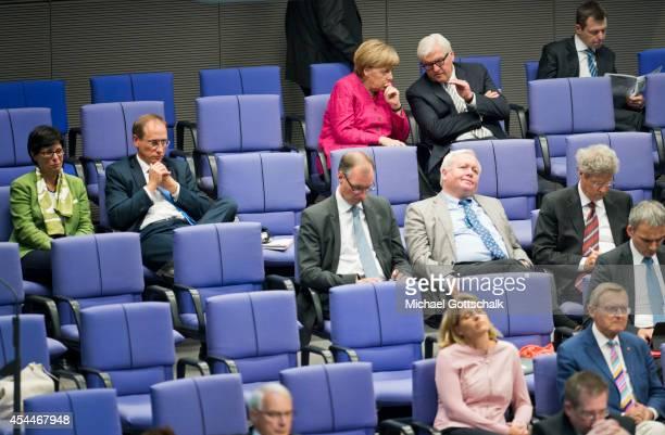 German Chancellor Angela Merkel and German Foreign Minister FrankWalter Steinmeier sit in last row behind members of parliament during debates...