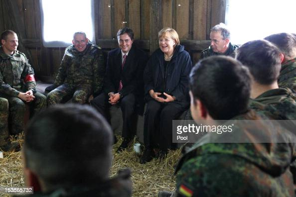 German Chancellor Angela Merkel and German Prime Minister David McAllister talk with soldiers in an excercise hut during their visit to the Munster...