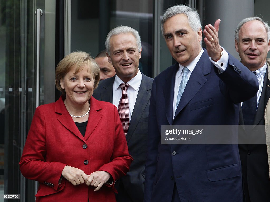 German Chancellor <a gi-track='captionPersonalityLinkClicked' href=/galleries/search?phrase=Angela+Merkel&family=editorial&specificpeople=202161 ng-click='$event.stopPropagation()'>Angela Merkel</a> and German Transport Minister Peter Ramsauer (2nd L) listen as <a gi-track='captionPersonalityLinkClicked' href=/galleries/search?phrase=Peter+Loescher&family=editorial&specificpeople=4296846 ng-click='$event.stopPropagation()'>Peter Loescher</a>, CEO of SIEMENS gestures upon their arrival for the German summit on electric mobility at the Hauptstadtrepraesentanz of Deutsche Telekom on May 3, 2010 in Berlin, Germany. The goal of the National development plan for electric mobility is to advance research and development, market preparation for and introduction of batterypowered vehicles in Germany.