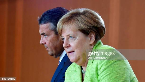German Chancellor Angela Merkel and German Vice Chancellor and German Foreign Minister Sigmar Gabriel get ready for the start of the weekly cabinet...