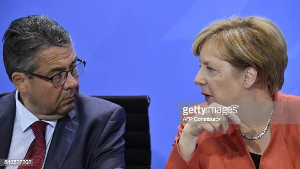 German Chancellor Angela Merkel and German Vice Chancellor and Foreign Minister Sigmar Gabriel talk during a press conference after a meeting with...