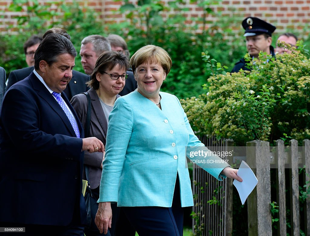 German Chancellor Angela Merkel and German Vice Chancellor, Economy and Energy Minister Sigmar Gabriel leave after a news conference following the weekly cabinet meeting that took place in the framework of a retreat meeting of the German cabinet at Meseberg Palace on May 25, 2016 in Meseberg near Gransee, northeastern Germany. / AFP / TOBIAS