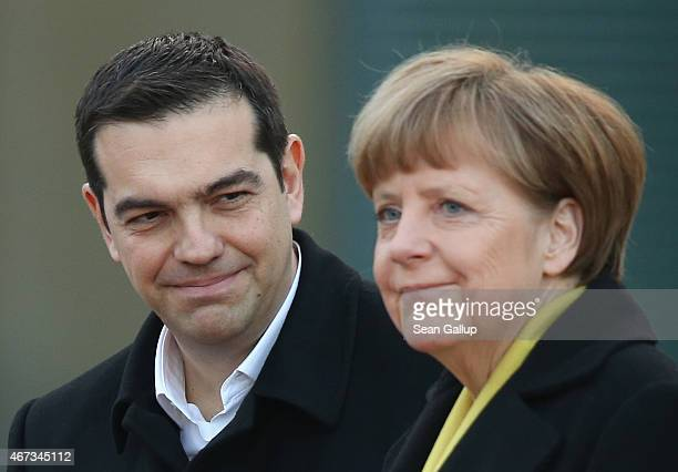 German Chancellor Angela Merkel and Greek Prime Minister Alexis Tsipras prepare to listen to their countries' national anthems upon his arrival for...