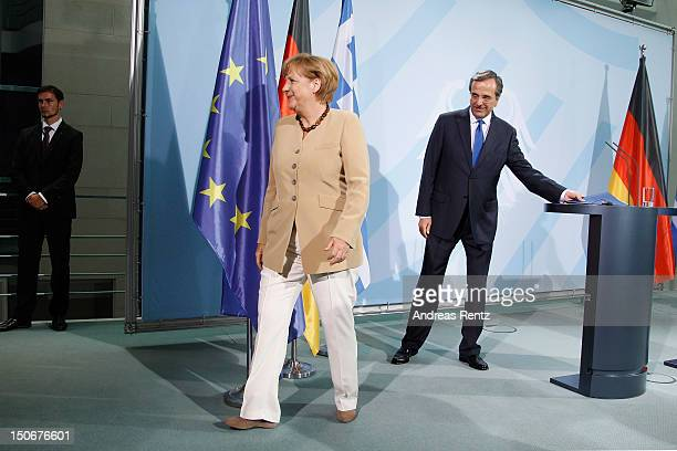 German Chancellor Angela Merkel and Greek Prime Minister Antonis Samaras leave after a press statement at the Chancellery on August 24 2012 in Berlin...