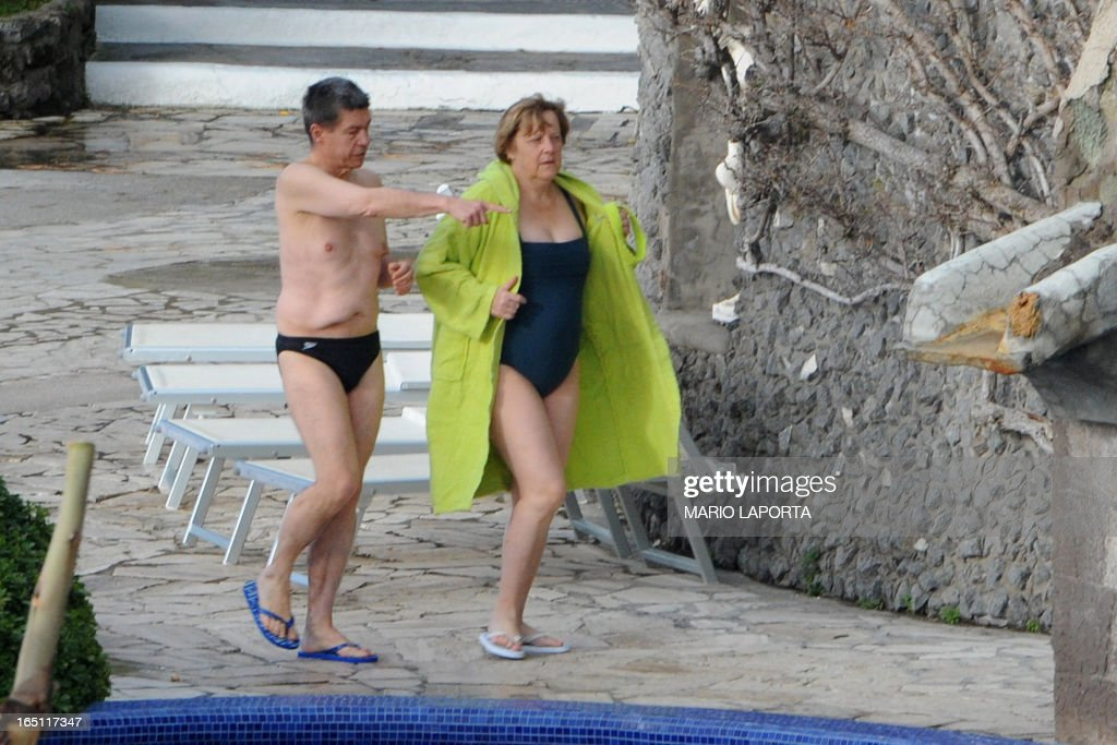 German Chancellor Angela Merkel (R) and her husband Joachim Sauer arrive to take a bath in the swimming pool of the Aphrodite Terme in the coastal town of Sant'Angelo d'Ischia on the southern Italy's Island of Ischia during their Easter holiday on March 31, 2013.