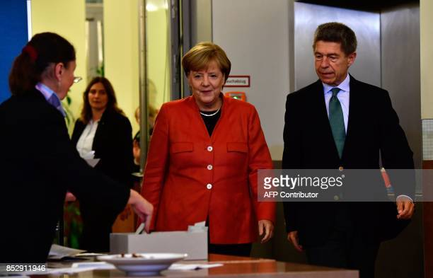 German Chancellor Angela Merkel and her husband Joachim Sauer arrive to cast their votes at a polling station in Berlin during general elections on...