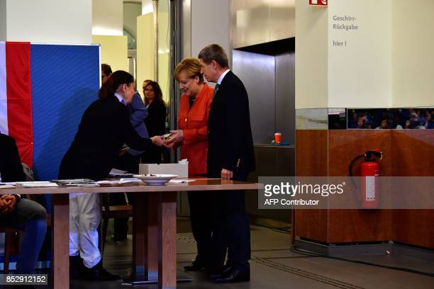 German Chancellor Angela Merkel and her husband Joachim Sauer get their ballot papers at a polling station in Berlin during general elections on...