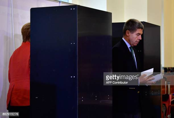 German Chancellor Angela Merkel and her husband Joachim Sauer prepare to cast their votes at a polling station in Berlin during general elections on...