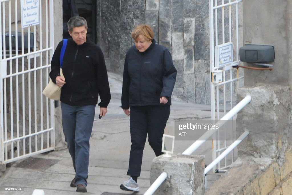 German Chancellor Angela Merkel (R) and her husband Joachim Sauer take a walk in the coastal town of Sant'Angelo d'Ischia on the Island of Ischia during their Easter holiday on March 30, 2013.
