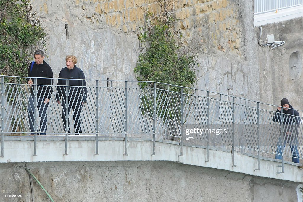 German Chancellor Angela Merkel and her husband Joachim Sauer take a walk in the coastal town of Sant'Angelo d'Ischia on the Island of Ischia during their Easter holiday on March 30, 2013.