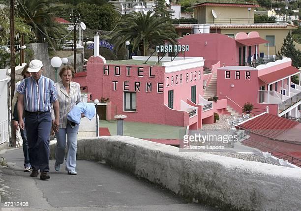 German Chancellor Angela Merkel and her husband Joachim Sauer walk beside the beach on April 11 2006 on the island of Ischia Italy