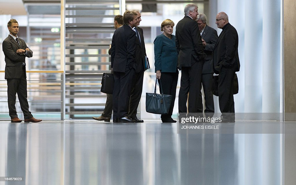 German Chancellor Angela Merkel (C) and her party colleagues from the Christian Democrats (CDU/CSU) make their way to the 2nd round of exploratory talks with the Green party on forming a coalition government in Berlin on October 15, 2013. The exploratory talks with the left-leaning ecologist party are part of Merkel's hunt for a governing partner after her conservatives won September 22 elections but fell short of a ruling majority.