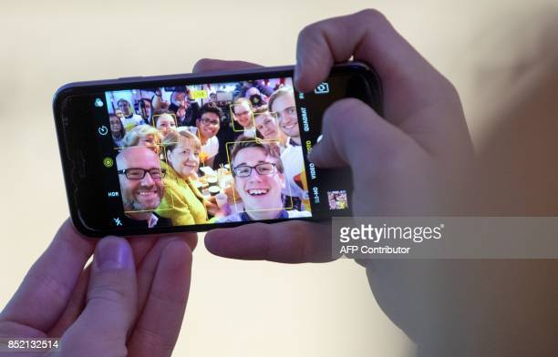 German Chancellor Angela Merkel and her party's secretary general Peter Tauber are displayed on a mobile phone as they pose with members of their...