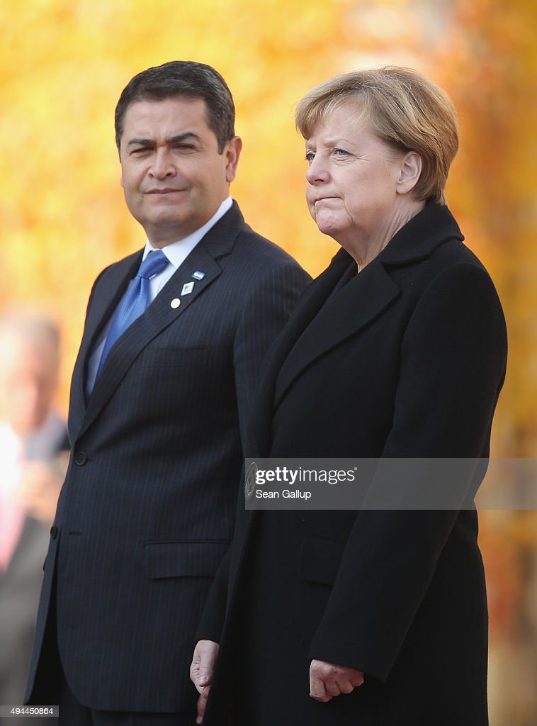 German Chancellor <a gi-track='captionPersonalityLinkClicked' href=/galleries/search?phrase=Angela+Merkel&family=editorial&specificpeople=202161 ng-click='$event.stopPropagation()'>Angela Merkel</a> and Honduran President Juan Orlando Hernandez listen to their countries' respective national anthems upon Hernandez's arrival for an official visit at the Chancellery on October 27, 2015 in Berlin, Germany. Merkel is seeking to unify European Union members under a common policy regarding the massive migrant influx, of which Germany will burden the largest share this year.