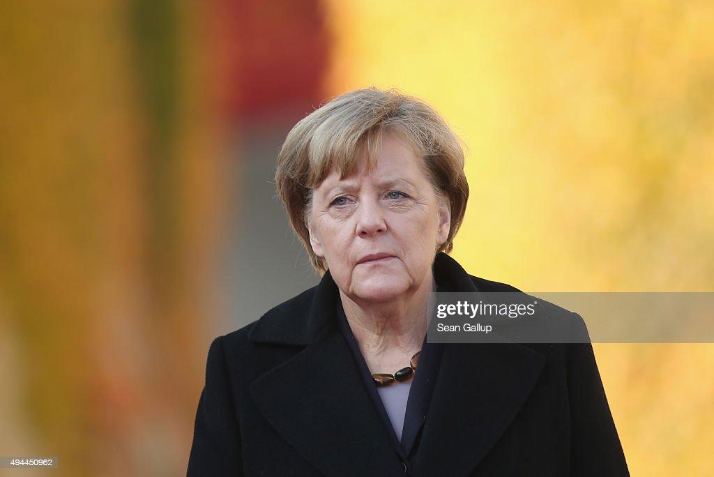 German Chancellor Angela Merkel and Honduran President Juan Orlando Hernandez prepare to review a guard of honour upon Hernandez's arrival for an...