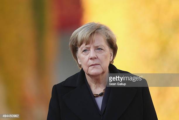 German Chancellor Angela Merkel and Honduran President Juan Orlando Hernandez prepare to review a guard of honour upon Hernandez's arrival for an...