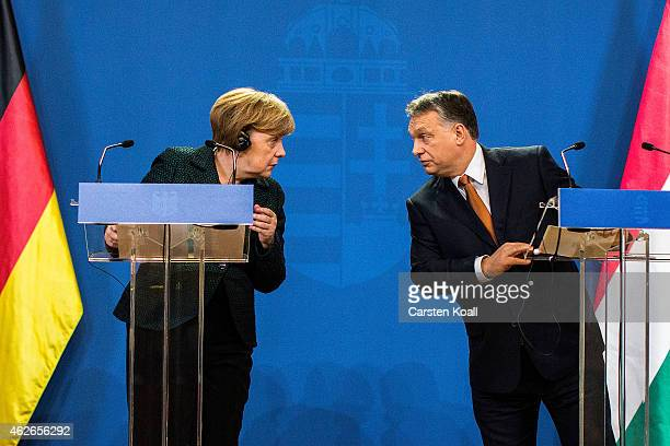 German Chancellor Angela Merkel and Hungarian Prime Minister Viktor Orban speak to each other following talks on February 2 2015 in Budapest Hungary...