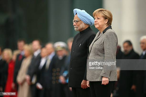 German Chancellor Angela Merkel and Indian Prime Minister Manmohan Singh listen to their nations' respective national anthems upon Singh's arrival at...