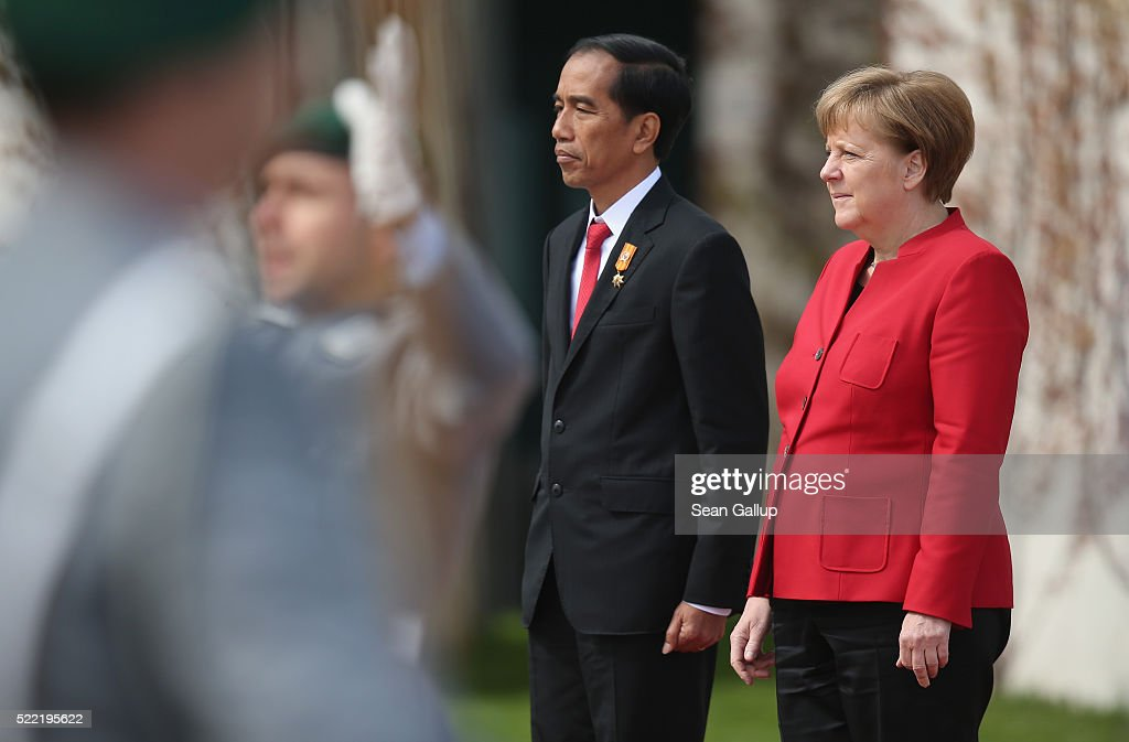 German Chancellor <a gi-track='captionPersonalityLinkClicked' href=/galleries/search?phrase=Angela+Merkel&family=editorial&specificpeople=202161 ng-click='$event.stopPropagation()'>Angela Merkel</a> and Indonesian President <a gi-track='captionPersonalityLinkClicked' href=/galleries/search?phrase=Joko+Widodo&family=editorial&specificpeople=6657368 ng-click='$event.stopPropagation()'>Joko Widodo</a> listen to a military band perform their nations' respect anthems upon his arrival at the Chancellery on April 18, 2016 in Berlin, Germany. President <a gi-track='captionPersonalityLinkClicked' href=/galleries/search?phrase=Joko+Widodo&family=editorial&specificpeople=6657368 ng-click='$event.stopPropagation()'>Joko Widodo</a> is visting Germany, Indonesia's biggest European trading partner, as part of a tour of European capitals.