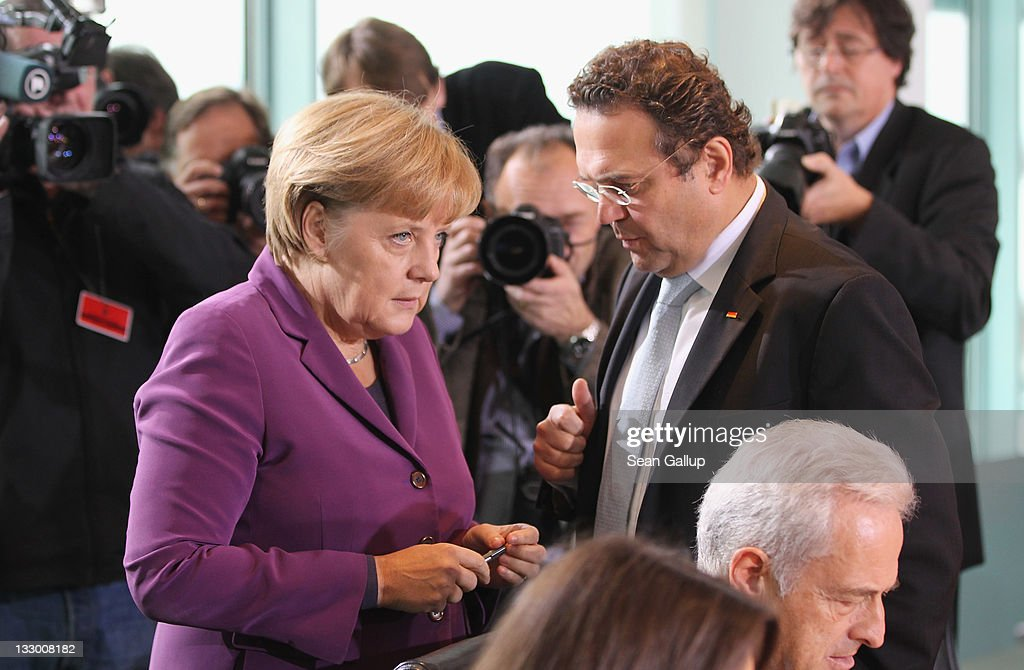 German Chancellor Angela Merkel and Interior Minister HansPeter Friedrich chat prior to the weekly German government cabinet meeting on November 16...