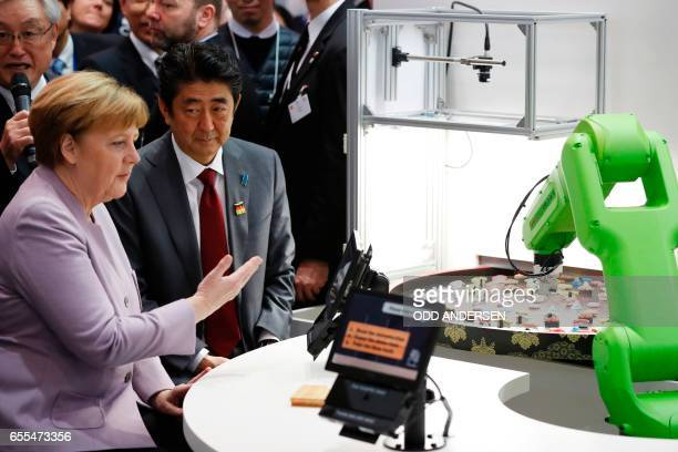 German Chancellor Angela Merkel and Japanese Prime Minister Shinzo Abe visit a booth with a robotic arm picking up sushis as they tour the Ce Bit...