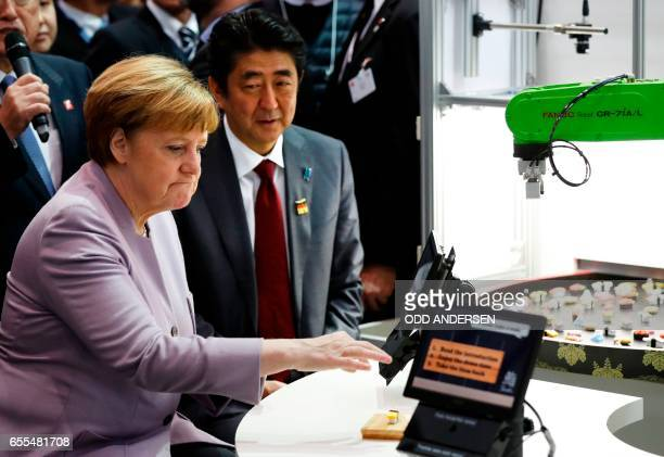 German Chancellor Angela Merkel and Japanese Prime Minister Shinzo Abe visit a booth with a robotic arm picking up sushis as they tour the CeBIT...