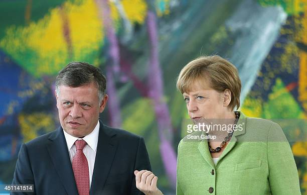 German Chancellor Angela Merkel and King Abdullah II of Jordan arrive to give statements to the media prior to talks at the Chancellery on June 24...
