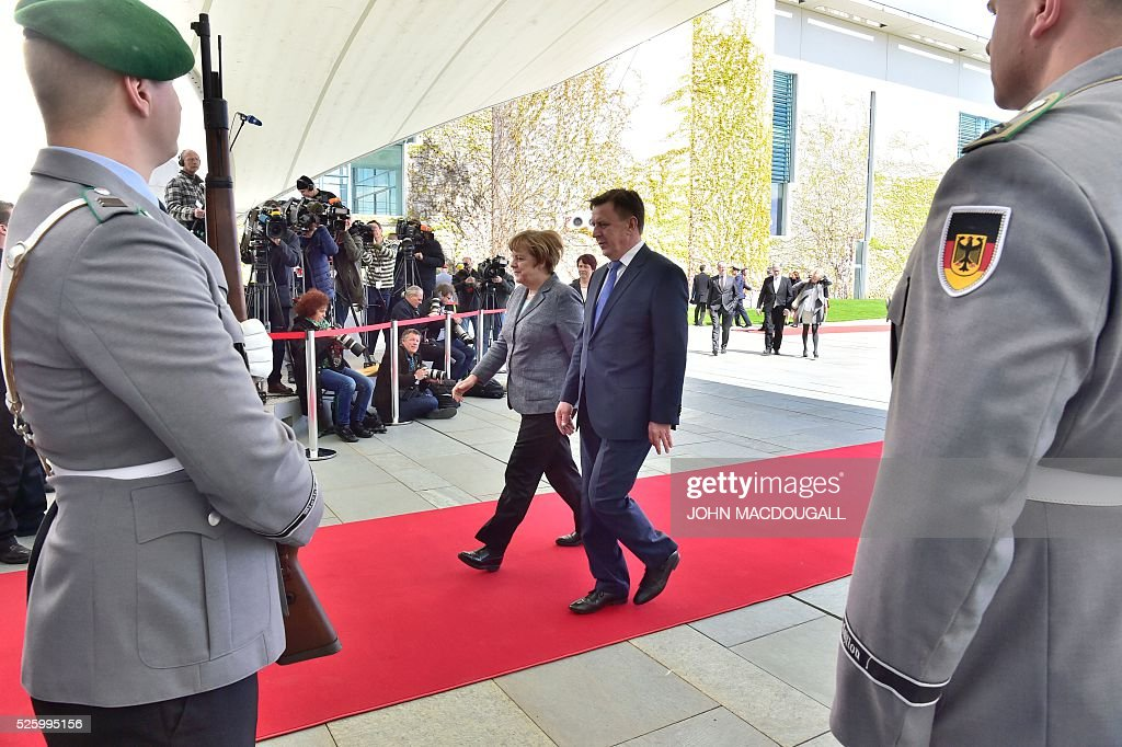 German Chancellor Angela Merkel (C-L) and Latvian Prime Minister Maris Kucinskis (C-R) walk over the red carpet after inspecting a military honor guard on April 29, 2016 in front of the Chancellery in Berlin. / AFP / John MACDOUGALL