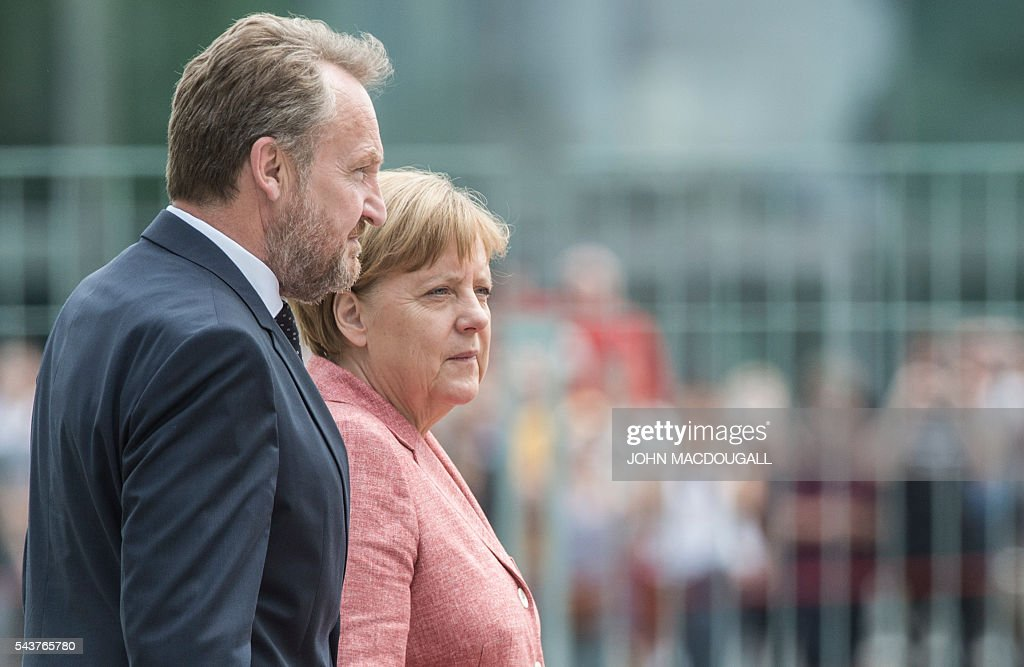 German Chancellor Angela Merkel (R) and member of the Presidency of Bosnia and Herzegovina, Bakir Izetbegovic, listen to their national anthems during a welcoming ceremony at the chancellery in Berlin on June 30, 2016. / AFP / JOHN