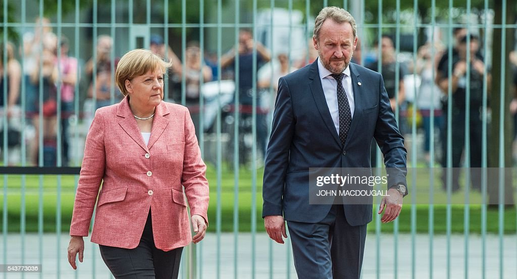 German Chancellor Angela Merkel (L) and member of the Presidency of Bosnia and Herzegovina Bakir Izetbegovic review an honour guard (unseen) during a welcoming ceremony at the chancellery in Berlin on June 30, 2016. / AFP / JOHN