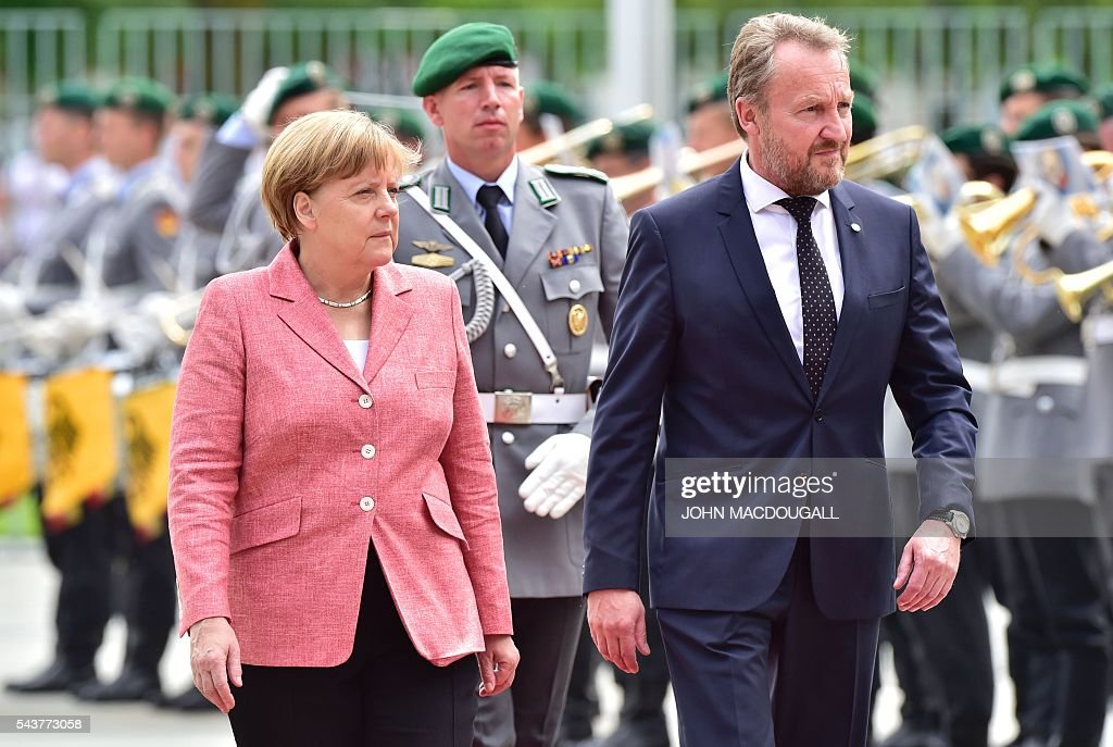 German Chancellor Angela Merkel (L) and member of the Presidency of Bosnia and Herzegovina Bakir Izetbegovic review an honour guard during a welcoming ceremony at the chancellery in Berlin on June 30, 2016. / AFP / JOHN