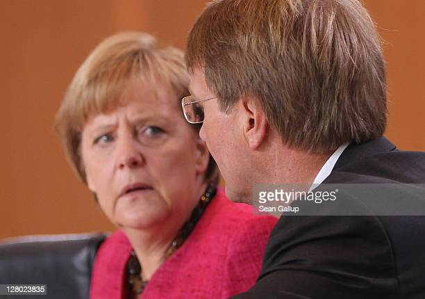 German Chancellor Angela Merkel and Minister of the Chancellery Ronald Pofalla arrive for the weekly German government cabinet meeting on October 5...