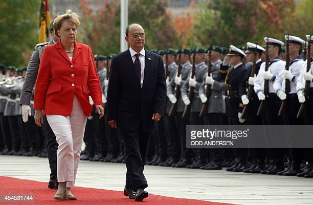 German Chancellor Angela Merkel and Myanmar President Thein Sein inspect a military honor guard in front of the Chancellery in Berlin on September 3...