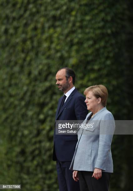 German Chancellor Angela Merkel and new French Prime Minister Edouard Philippe listen to their nations' naitonal anthems performed by a guard of...