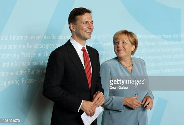 German Chancellor Angela Merkel and new German government spokesman Steffen Seibert pose for photographers at Seibert's official presentation as new...