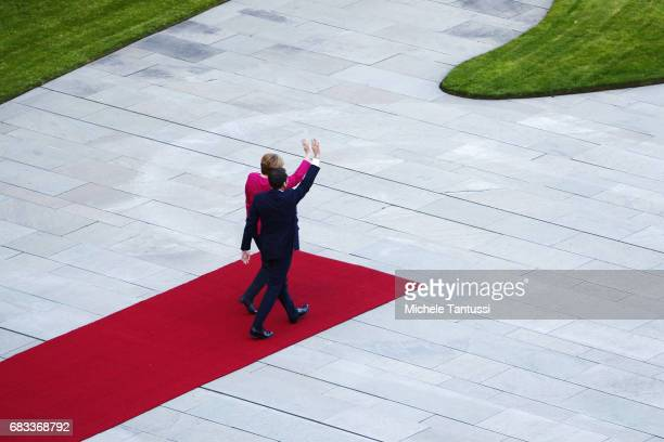German Chancellor Angela Merkel and newlyelected French President Emmanuel Macron wave in the courtyard of the Chancellery on May 15 2017 in Berlin...