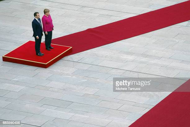 German Chancellor Angela Merkel and newlyelected French President Emmanuel Macron listen to the national anthems in the courtyard of the Chancellery...