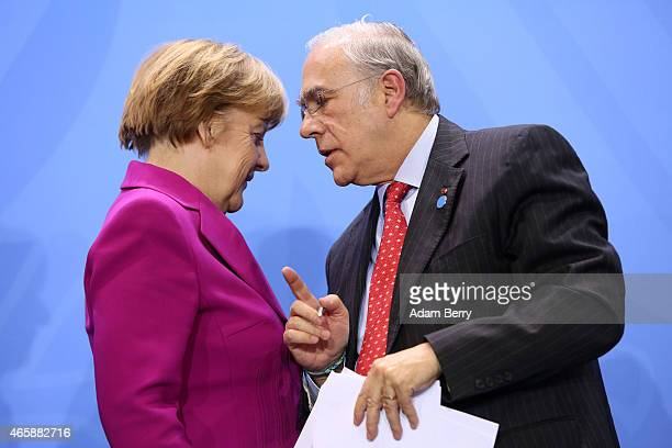 German Chancellor Angela Merkel and Organisation for Economic Cooperation and Development SecretaryGeneral Angel Gurria leave a press conference at...