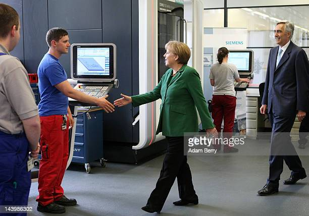 German Chancellor Angela Merkel and Peter Loescher chief executive officer of German Siemens AG greet trainees at a milling machine station at a...