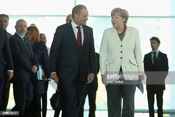 German Chancellor Angela Merkel and Polish President Donald Tusk arrive to give statements to the media upon Tusk's arrival at the Chancellery on...