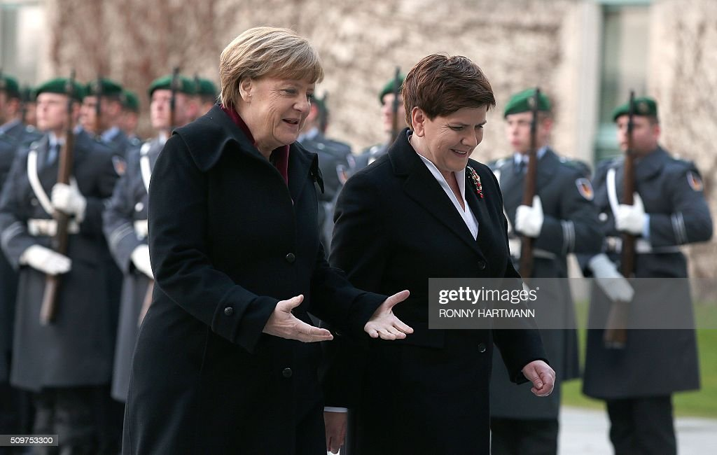 German Chancellor Angela Merkel (L) and Polish Prime Minister Beata Szydlo inspect a guard of honor during a welcoming ceremony at the Chancellery in Berlin on February 12, 2016. / AFP / Ronny Hartmann