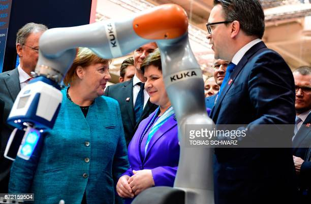German Chancellor Angela Merkel and Polish Prime Minister Beata Szydlo stand behind a robot of Kuka during a visit at the Hannover Messe trade fair...