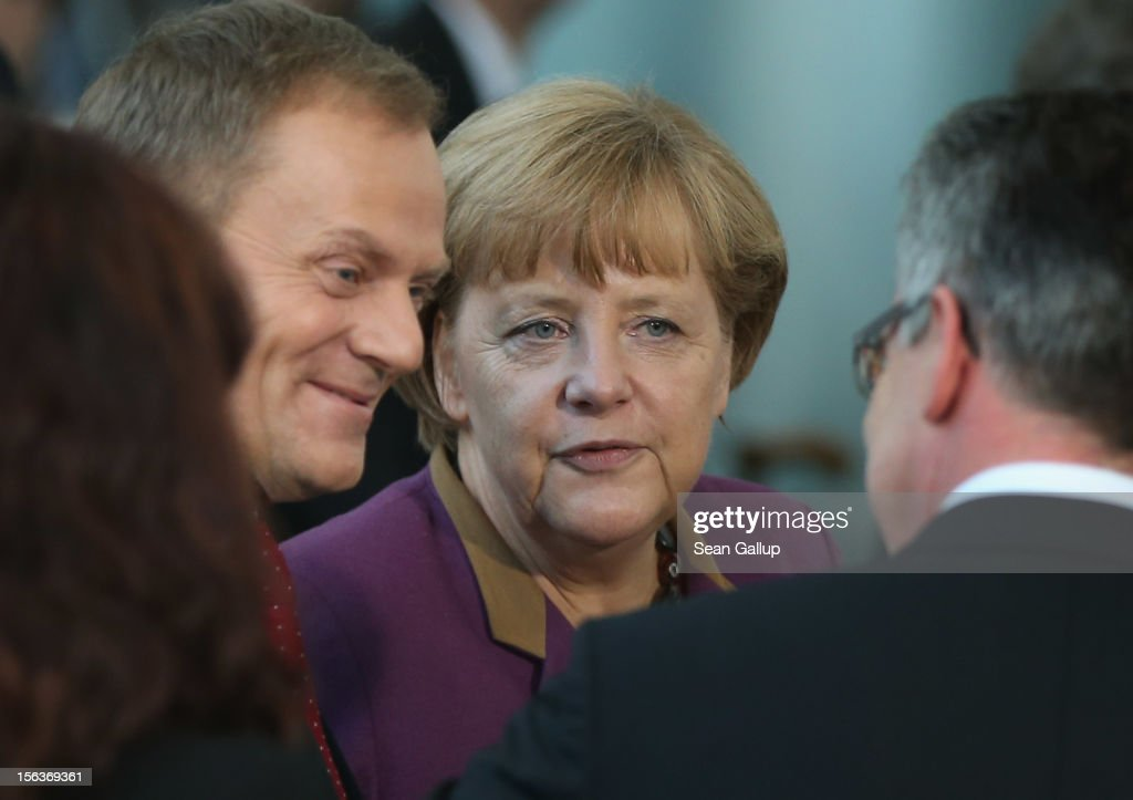 German Chancellor <a gi-track='captionPersonalityLinkClicked' href=/galleries/search?phrase=Angela+Merkel&family=editorial&specificpeople=202161 ng-click='$event.stopPropagation()'>Angela Merkel</a> and Polish Prime Minister <a gi-track='captionPersonalityLinkClicked' href=/galleries/search?phrase=Donald+Tusk&family=editorial&specificpeople=870281 ng-click='$event.stopPropagation()'>Donald Tusk</a> (L) depart after posing for a group photo pf the German and Polish delegations at the Chancellery on November 14, 2012 in Berlin, Germany. Tusk and his delegation are in Berlin for German-Polish government consultations.