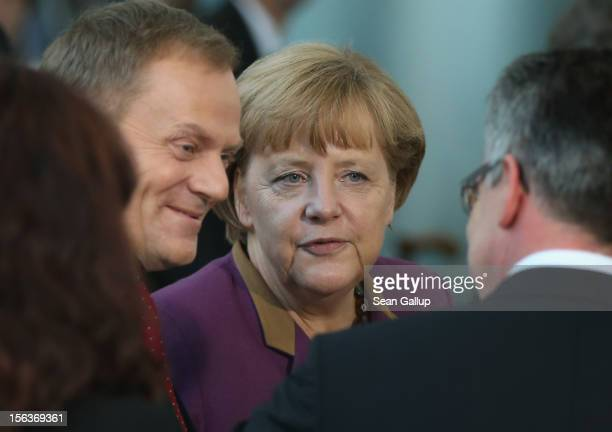 German Chancellor Angela Merkel and Polish Prime Minister Donald Tusk depart after posing for a group photo pf the German and Polish delegations at...