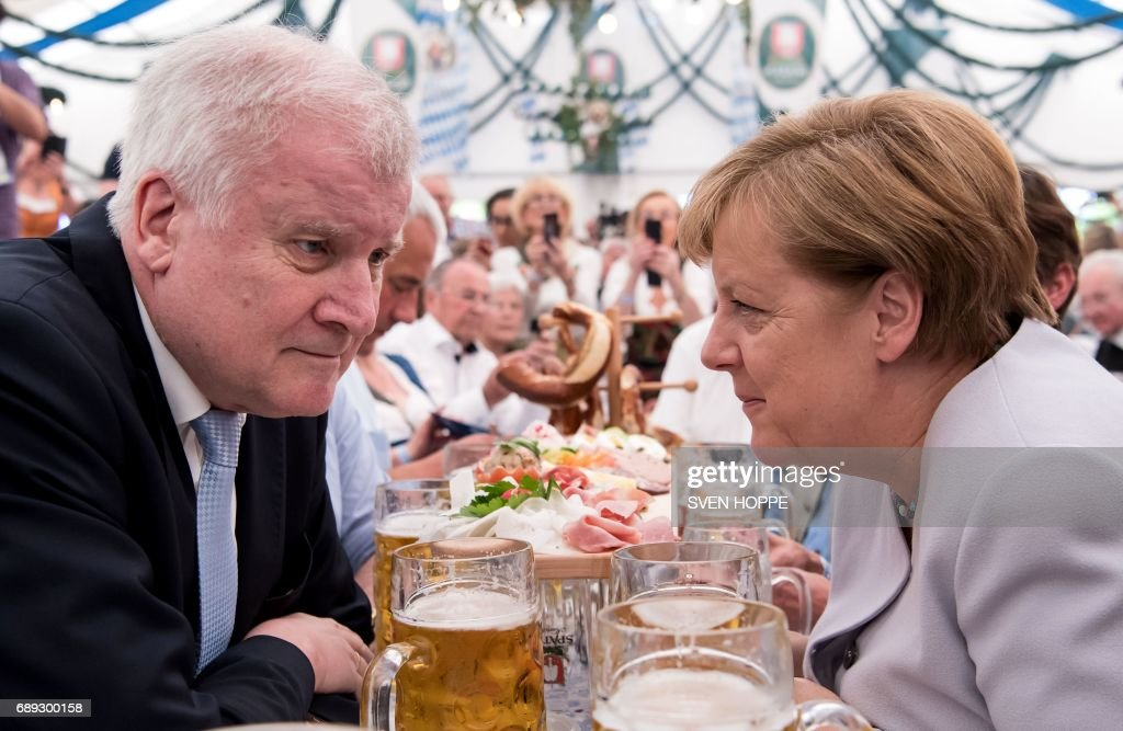 German Chancellor Angela Merkel (R) and premier of the German state of Bavaria, Horst Seehofer sit in a beer tent during a joint campaigning event of the Christian Democratic Union (CDU) and the Christion Social Union (CSU) in Munich, southern Germany, on May 27, 2017. / AFP PHOTO / dpa / Sven Hoppe / Germany OUT