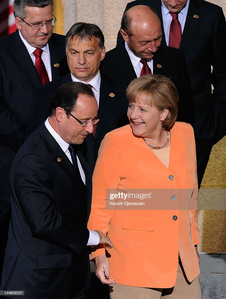 German Chancellor Angela Merkel (R) and President of France Francois Hollande collide as they walk off the riser after the family photo under the Soldier Field colonnades during the NATO Summit on May 20, 2012 in Chicago, Illinois. As sixty heads of state converge for the two day summit that will address the situation in Afghanistan, among other global defense issues, thousands of demonstrators have taken to the streets to protest.